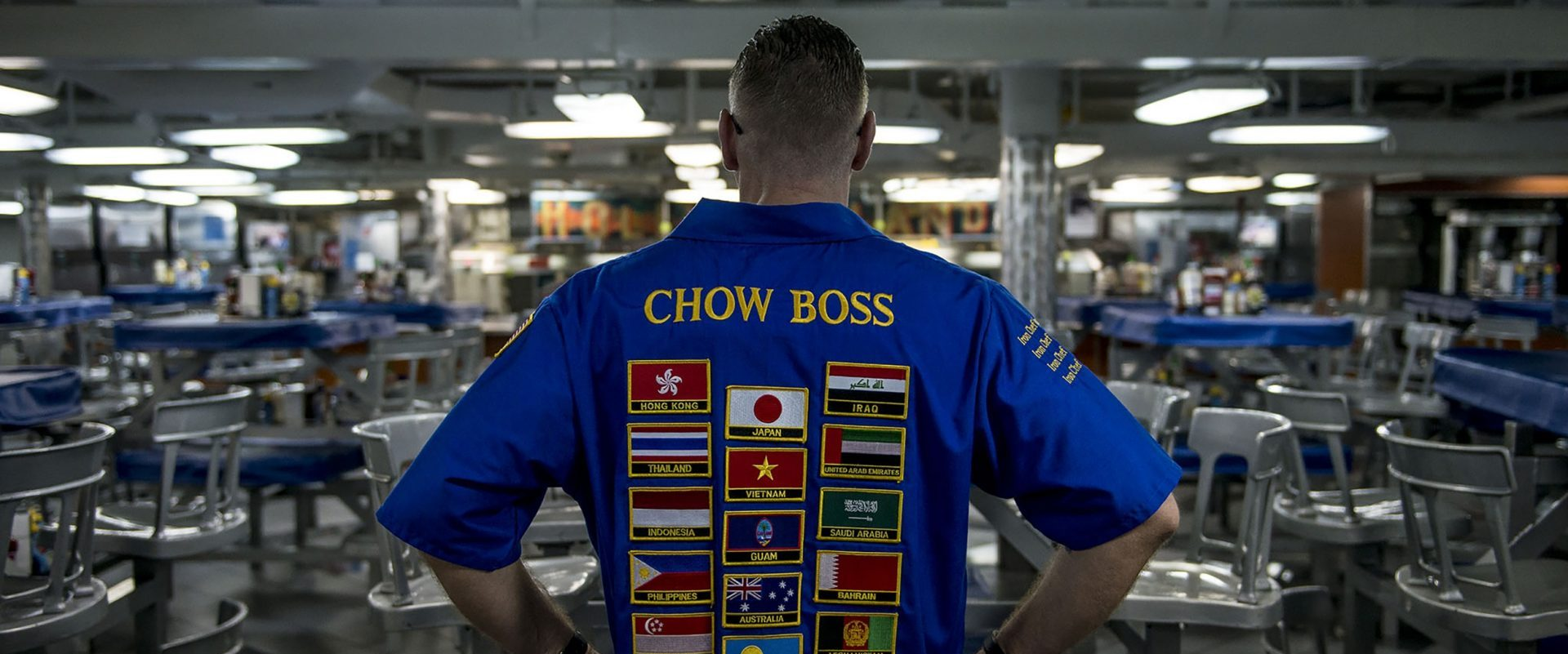 Recipes, Navy cook with Chow Boss embroidered on back of shirt, looking over cafeteria