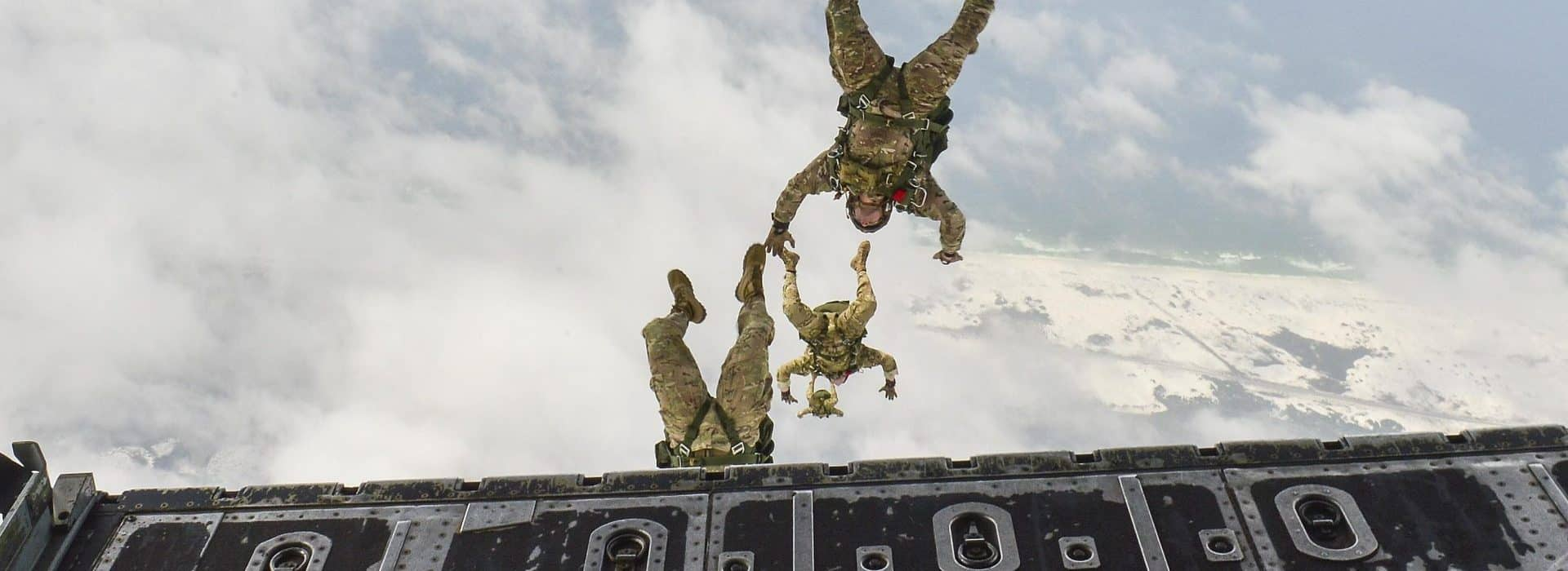 The DET header, three paratroopers jumping from rear ramp of aircraft.